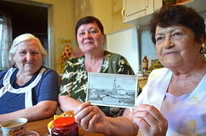 """Drei wolgadeutsche Frauen in Marx: Sinaida Sterz (rechts) mit ihren Freundinnen Lidija (links) und Elsa (Mitte) und einem alten Foto mit der lutherischen Kirche, als sie noch ihren Glockenturm und die Kuppel besaß. / Tino Künzel <br> Eingestellt am: 07.07.2014, <a style=""""text-shadow: 0px 0px 0;"""" href=http://www.rusdeutsch.eu/?news=2411 target=_blank >lesen</a>, <a style=""""text-shadow: 0px 0px 0;"""" href=http://www.rusdeutsch.eu/fotos/2347_b.jpg target=_blank >herunterladen</a>"""